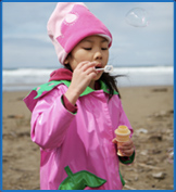 Little girl blowing bubbles in Yachats, Oregon
